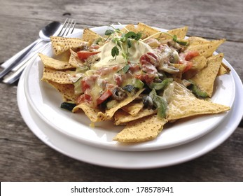 Nachos on white plate on wooden table