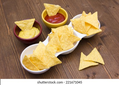 Nachos with sauces on wooden table