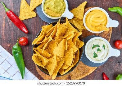 Nachos - yellow corn chips with various sauces in bowls: guacamole, cheese sauce, white sauce, on a wooden table. Mexican food concept. The view from the top.