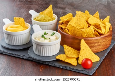 Nachos - yellow corn chips with various sauces in bowls: guacamole, cheese sauce, white sauce, on a wooden table. Mexican food concept.
