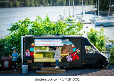 NACKA, SWEDEN - JUNE 28, 2019: Front view of customers at a food truck near a small harbor with sea and boats in the background in Nacka Sweden June 28, 2019.