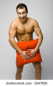 Nacked Smile Man Standing Trying To Hide His Body By Red Pillow
