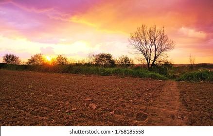 Pełen kolorów zachód słońca nad zaoranym polem uprawynym. Ciełe światło, bajeczny krajobraz - Shutterstock ID 1758185558