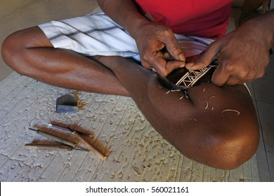 NADI, FIJI - DEC 31 2016:Hands of Indigenous Fijian man wood carving a sea turtle. In Fiji sea turtles symbolizes good luck.