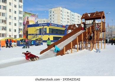 Nadym, RUSSIA-MARCH 14, 2021: Children have fun and ride down the slide on a sunny frosty day during the Maslenitsa holiday