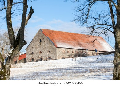 NAEAEAS,FLODA, SWEDEN, FEBRUARY 2016, a big. old stone stable seen from down a hill on a cold but beautiful winter day with snow on the ground.