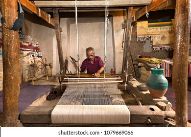 NAEIN, IRAN - APRIL 8, 2018: Iranian man weaves fabrics known as Aba, in traditional way, in the town of Naein, Iran.