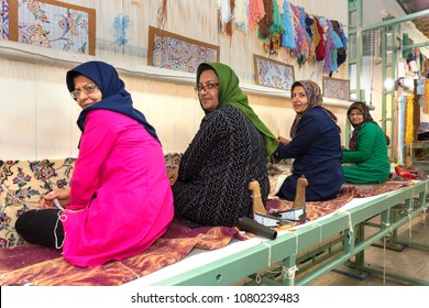 NAEIN, IRAN - APRIL 8, 2018: Iranian women waves persian rugs in the carpet workshop in Naein, Iran.