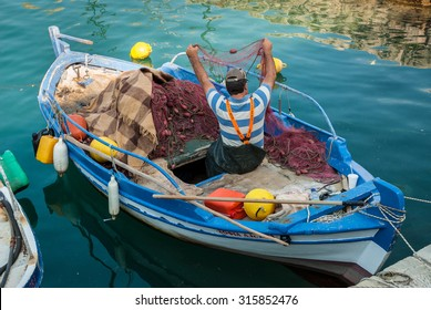 NAFPAKTOS, GRRECE - JUNE 17, 2013: An unidentified man prepares his fishing nets in his boat. Fishing in traditional boats remains an important part of the local economy in some small cities of Greece