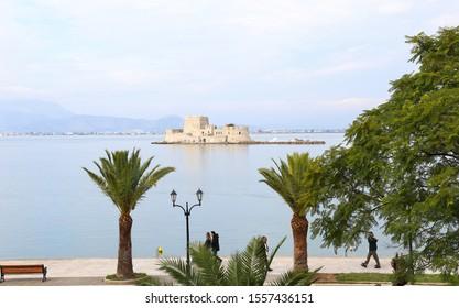NAFPLIO GREECE, NOVEMBER 18 2018: people walking at Nafplio harbor in front of the Bourtzi castle Argolis Greece. Editorial use.