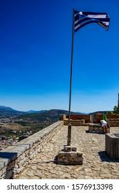NAFPLIO, GREECE - OCTOBER 2015: The Hellenic flag waving over the historical Palamidi fortress against a deep blue sky. Nafplio city, Argolis, Greece, Europe