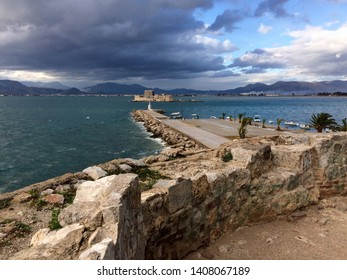 Nafplion argolis greece. View from fortification. Winter. broken clouds. Rough sea. Fortification of bourtzi in the sea. Light house in port entry. stones of fortification. Sunset light. Mountains