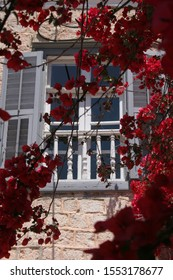 Nafplion Greece. Window of neoclassic building with bugambilia flowers. Grey shutters and white banister. Venetian city.