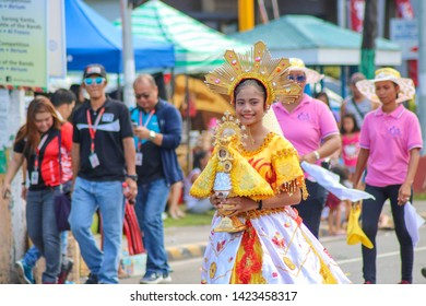 NAGA CITY, PHILIPPINES - CIRCA SEPTEMBER 2018: A young woman carrying Nuestra Señora de Penafrañcia Statue, a miraculous wooden statue of the Blessed Virgin, during the Peñafrancia Festival.