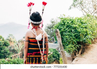 Naga girl in colorful traditional indigenous clothes in the village looking at mountains