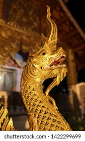 A Naga head at Naga steps, Wat Pha singh, Chiang mai, Thailand, looks alive, illuminating brightly and faithfully during nighttime. Naga head isolated with Blurred background.