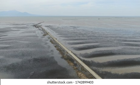 Nagabeta Seabed Road in Kumamoto Prefecture, Japan taken with drone. At low tide, a roadway for fishing appears and traffic is possible. At high tide, it is submerged and electric poles line the sea.