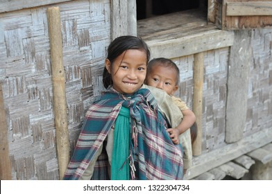 Nagaland, India - March 2012: Cute little girl carries her younger brother on her back in Nagaland, remote region of India. Documentary editorial.