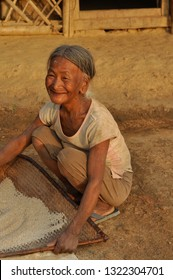 Nagaland, India - March 2012: Happy old woman sifts flour in Nagaland, remote region of India. Documentary editorial.