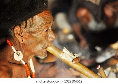 Nagaland, India - March 2012: Old man with traditional necklace and painted face smokes pipe in Nagaland, remote region of India. Documentary editorial.
