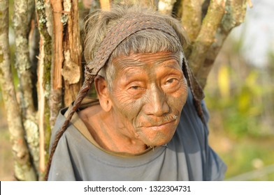 Nagaland, India - March 2012: Portrait of old man carrying heavy load in Nagaland, remote region of India. Documentary editorial.