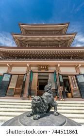 "Nagano City, Japan - August 04, 2017 - Komainu (Lion-dog) over Jokoro (incense burner), Saisenbako (Offering box) and ""Chureiden"" inscription at Zenko-ji war memorial pagoda"