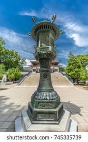 "Nagano City, Japan - August 04, 2017 - ""Dedication"" inscription in Bronze Lantern (Tourou) in front of  Nihon Chureiden Shrine, the war memorial pagoda at Zenko-ji temple"