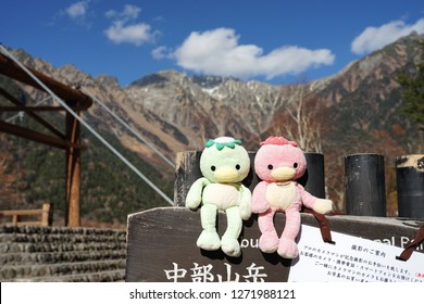 Nagano, Japan- 8 November,2018 : Kuppa dolls sitting on the timber signage with Kuppa bridge and beautiful Kamikochi Japan alps mountain background on 8 November,2018 in Nagano, Japan