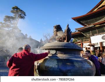 Nagano, Japan - Dec 29, 2015. People praying at Zenkoji Temple in Nagano, Japan. Zenko-ji is one of the most important and popular temples in Japan.