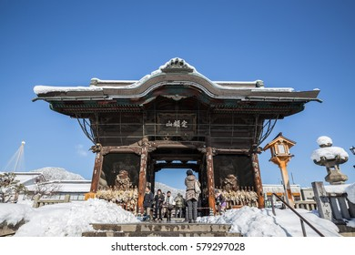 Nagano, JAPAN - January 18, 2017: big door of the Zenkoji Japanese temple with tourists on the sunshine day with clear blue sky in the winter with snow on the ground