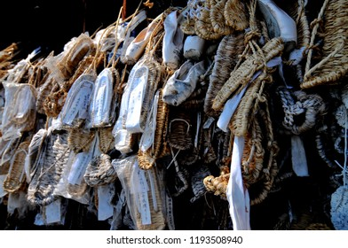 NAGANO, JAPAN - JULY 18, 2018 : Straw sandals (Waraji) and Ballet slippers hanging as offerings in front of the Niomon Gate at Zenko-ji temple in Nagano City, Japan