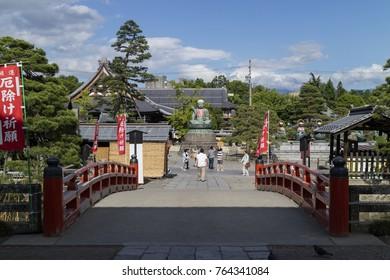 Nagano - Japan, June 3, 2017:  Bridge at the  Buddhist Zenkoji temple leading to the Bronze Nurebotoke, Wet Mizo Statue