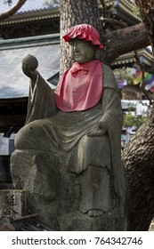 Nagano, Japan -  June 3, 2017: Traditional stone carved Jizo with red skirt and hat and a wish-fulfilling jewel in his hand at the Zenkoji temple