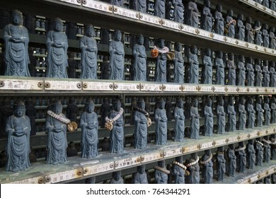 Nagano, Japan -  June 3, 2017: Rows of traditional stone carved miniature Buddhist statues with offerings at the Zenkoji temple