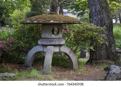 Nagano, Japan -  June 3, 2017: Stone lantern vovered with moss in the park around the Zenkoji temple