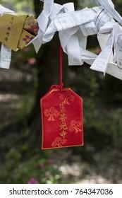 Nagano - Japan, June 3, 2017: Red Omamori or lucky charm hanging near the important Buddhist Zenkoji temple
