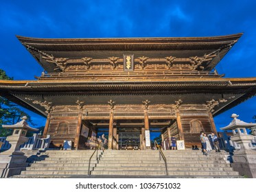 Nagano Prefecture, Japan - August 3, 2017: Motion blurred people walking along Sanmon Gate during blue hour before night at Zenko-ji Temple complex in Nagano city