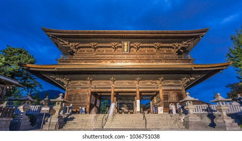 Nagano Prefecture, Japan - August 3, 2017: Panoramic view of Motion blurred people walking along Sanmon Gate during blue hour before night at Zenko-ji Temple complex in Nagano city