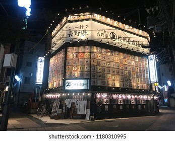 Nagano, Nagano Prefecture/Japan - July 11, 2018: A sake emporium all lit up at night with a patron's bicycle leaning against the side in downtown Nagano