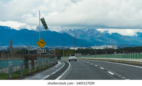 NAGANO,JAPAN - APRIL 15,2018 ; View  of Japan expressway in the Chubu region through the windshield from driving car to Matsumoto city under cloudy sky with mountain background.