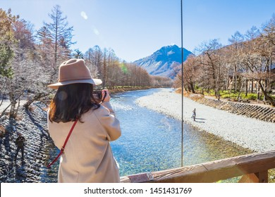 NAGANO,JAPAN-NOVE3MBER 15,2018: Women tourist take photo at the Kappa wodden bridge at Kamikochi, the northern part of the Japan Alps. Beautiful scenery .There are many natural and adventure