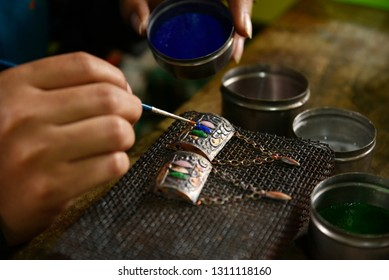 Nagaon, Assam, India. February 11, 2019. Women puts Mina on silver jewellery in a traditional method in a Assamese jewellery manufacturing unit.