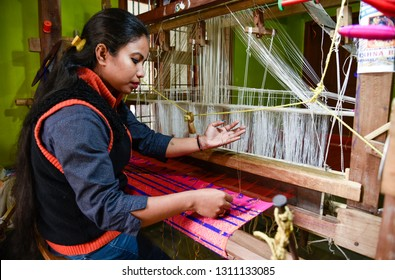Nagaon, Assam, India. February 11, 2019. Women weaving Assamese silk costumes in a traditional method in a manufacturing unit at Nagaon, Assam.