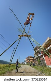 NAGARKOT - OCT 22: Nepalese people play on the swing on 22 October, 2014 in Nagarkot, Nepal. Playing on the swing is part of a religious celebration (Dashain)  to celebrate the end of the rainy season
