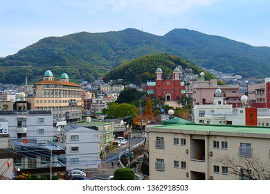 Nagasaki, Japan - November 28, 2014 : The Urakami Cathedral, a Symbol of Nagasaki, surrounded by buildings with mountain background.