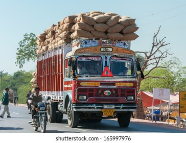 NAGAUR, INDIA - CIRCA FEBRUARY 2011: Overloaded dump truck filled with jute bags on the road.