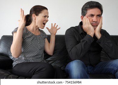Nagging wife (age 30) complains to her husband (age 40) at home. Real people. Relationship lifestyle. Copy space