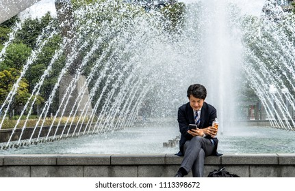 Nagoya, Aichi Prefecture / Japan - April 18 2018: Young japanese salaryman sitting in a park and browsing mobile phone