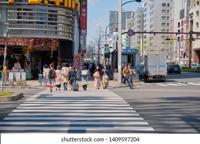 NAGOYA, JAPAN - APRIL 15, 2019: People crossing the road at crosswalk in front of Don Quijote Sakae, Don Quijote is convenience store with groceries and household items, Nagoya, Japan