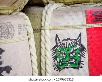 NAGOYA, JAPAN - MARCH 28, 2018: Close-up detail of Sake barrel with a painted green ogre, also known as Oni, as a logo. Kazaridaru, Shinto offerings, Atsuta Shrine. Travel and religion.